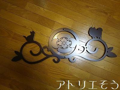 アトリエそう オーダーメイドデザインの丸に横木瓜家紋に犬と猫を加えて素敵にデザインしたロートアイアン風ステンレス製の妻飾り