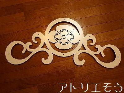 アトリエそう オーダーメイドデザインの丸に横木瓜の家紋に唐草を組み合わせたロートアイアン風のステンレス製妻飾りです。アイボリー塗装