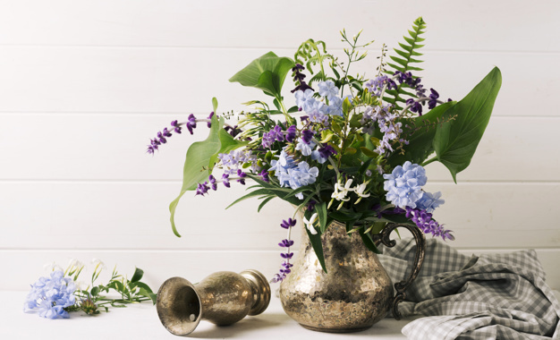 bouquet-of-blooms-in-vase-near-pitcher-on-table_23-2148029223.jpg