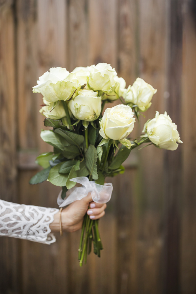 close-up-of-bride-s-hand-holding-bouquet-of-roses-against-wooden-backdrop_23-2147936632.jpg