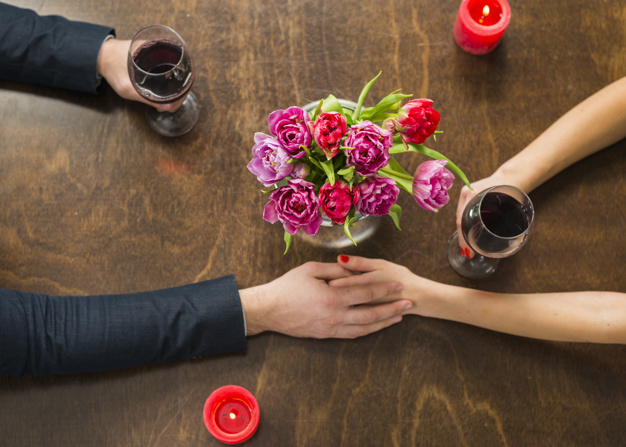 man-holding-hands-with-woman-at-table-with-glasses-and-flowers_23-2148024579.jpg