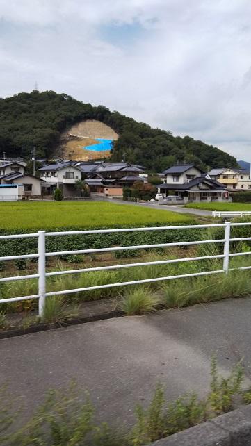 、岡山県の中国職業能力開発大学校内の倉敷市災害ボランティアセンタ-トラック移動中で車内から写しました。土砂崩れを起こした山