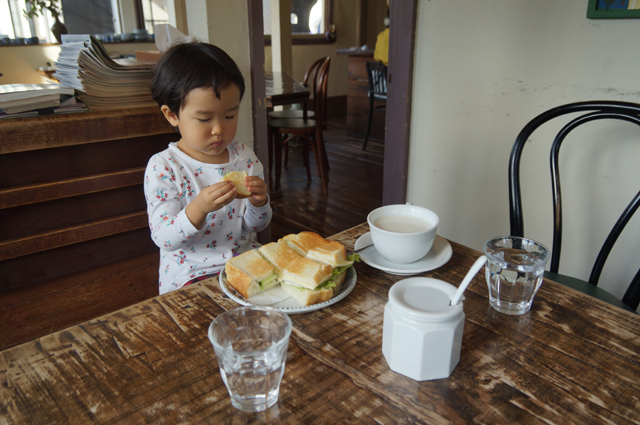 子供、サンドイッチを食べる