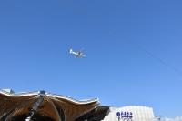 青空に着陸態勢の飛行機181026